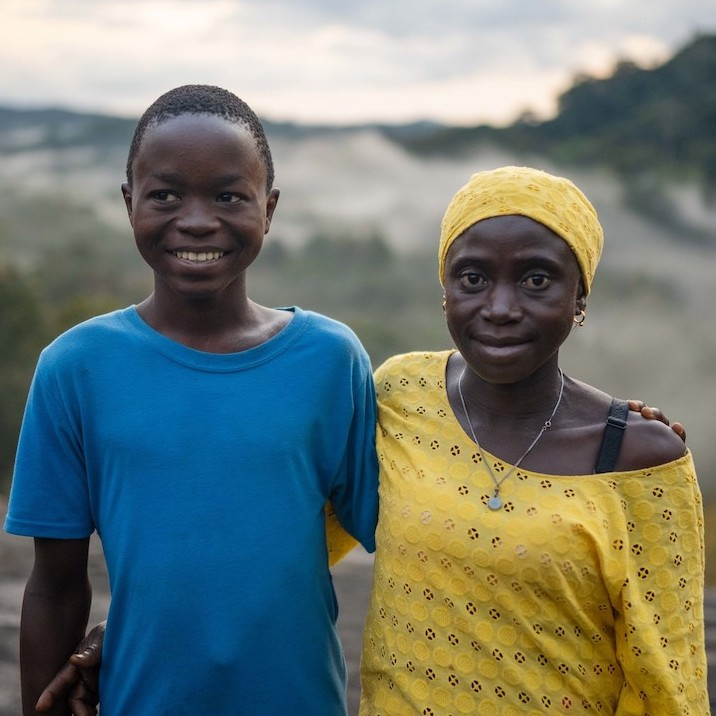 Lucia Mansaray and her son, Beshey. Lucia is a member of Fairtrade cocoa co-operative called Ngoleagorbu in Sierra Leone. Lucia is a cocoa farmer and lives in a community on the edge of the Gola rainforest, sharing her forest home with chimpanzees, hundreds of rare bird species and the elusive pygmy hippo, of which only 3,000 remain. In 2019, Lucia and hundreds of other cocoa farmers here came together through Fairtrade to form the Ngoleagorbu Union of Cocoa farmers, where passions for social and environmental justice run deep. Lucia is passionate and hopeful about what the future holds for her family and Ngoleagorbu, and her drive for change has led her to be chairperson of the Fairtrade Premium Committee.