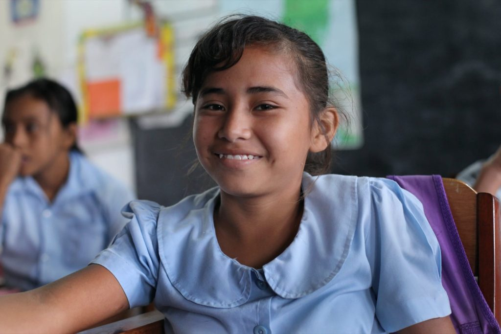 A student smiles during class at the San Narciso Roman Catholic school.